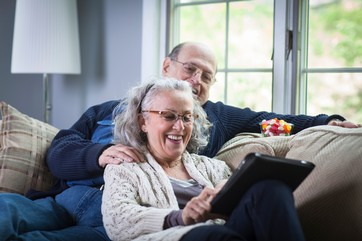 Senior couple using digital laptop on sofa at home