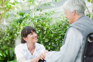 Nurse talking to older patient outdoors
